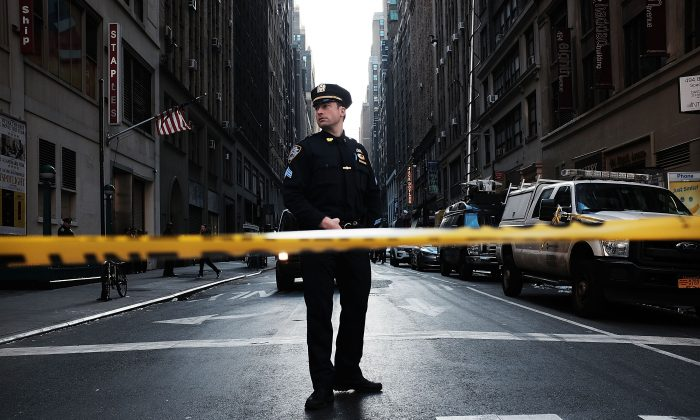 A police offficer stand at the scene of a midtown shooting that left one dead with two others wounded in New York City on Nov. 9, 2015. (Spencer Platt/Getty Images)