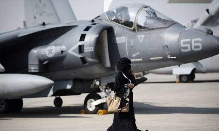 A Saudi woman walks past a US airplane during the opening of the Bahrain International Airshow on  January 21, 2016.(MOHAMMED AL-SHAIKH/AFP/Getty Images)