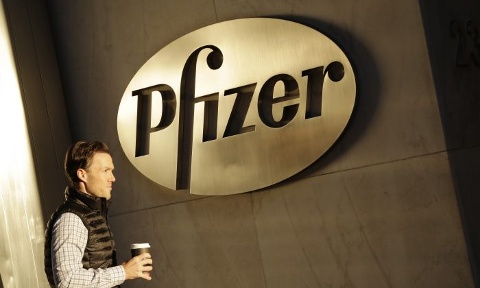 FILE - In this Monday, Nov. 23, 2015, file photo, a man enters Pfizer's world headquarters, in New York. U.S. Republican presidential candidate Donald Trump is railing about what's wrong in corporate America as he woos voters fed up with the status quo. He is blasting drugmaker Pfizer's tax-saving plan to move its headquarters overseas, refusing to eat Oreo cookies made in Mexico and vowing to get Apple to make iPhones in the U.S. His tirades about unfair competition, tax evasion and lost jobs trumpet a familiar tune, but going further than many others running for president have dared. (AP Photo/Mark Lennihan, File)