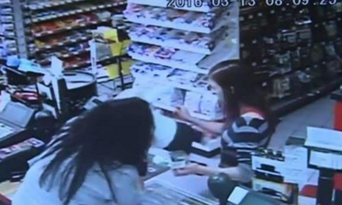 THE MOMENT: The cashier grabbed the baby right as the woman collapsed (YouTube/screenshot)