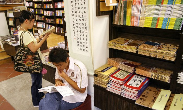 Chinese university students look at textbooks at a bookstore during the summer holidays in Shanghai, 16 August 2007. (Mark Ralston/AFP/Getty Images)
