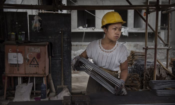 A Chinese female construction worker works at the building site of a new apartment complex in Beijing on Aug. 29, 2014. (Kevin Frayer/Getty Images)