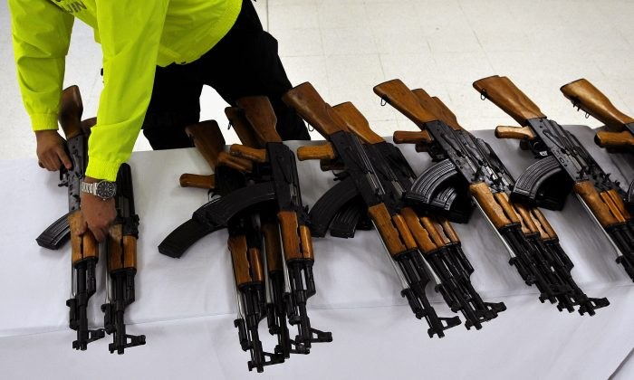 A Colombian police officer arranges assault rifles seized in Cali, Valle del Cauca department, Colombia on July 29, 2011. The Colombian police seized 47 Chinese-made 7.62mm Norinco assault rifles (AK-47 replicas) and 214 magazines. (Luis Robayo/AFP/Getty Images)