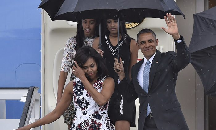 US President Barack Obama waves next to First Lady Michelle Obama (L) and their daughters Malia (L, behind) and Sasha upon their arrival at Jose Marti international airport in Havana on March 20, 2016. (Yuri Cortez/AFP/Getty Images)
