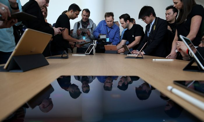 """CUPERTINO, CA - MARCH 21:  Attendees look at the new 9.7"""" iPad Pro during an Apple special event at the Apple headquarters on March 21, 2016 in Cupertino, California. Apple CEO announced the iPhone SE and a 9.7"""" version of the iPad Pro.  (Photo by Justin Sullivan/Getty Images)"""