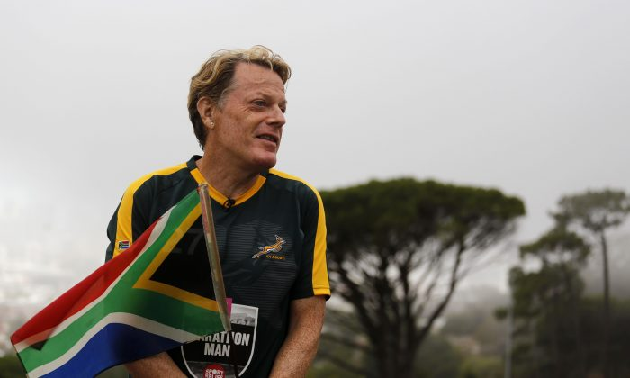British comedian Eddie Izzard holds a South African flag at the foot of Table mountain in Cape Town, South Africa, Friday, March. 18,  2016. Eddie Izzard is attempting to complete 27 marathons in 27 days across South Africa by Sunday, as part of his charity drive.  (AP Photo/Schalk van Zuydam)
