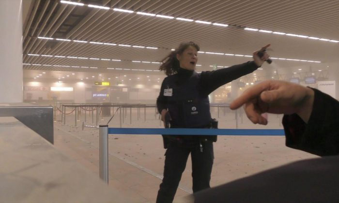 A police officers directs passengers in a smoke filled terminal at Brussels Airport, in Brussels after explosions on March 22. (Ralph Usbeck via AP)