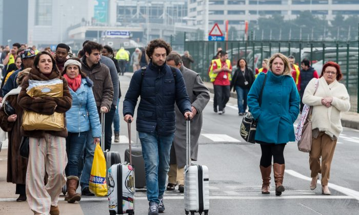 People walk away from Brussels airport after explosions rocked the facility in Brussels, Belgium Tuesday March 22, 2016.   (AP Photo/Geert Vanden Wijngaert)