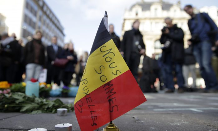 "A Belgian flag reading ""We are all Brussels"" stands at a makeshift memorial at Place de la Bourse (Beursplein) following attacks in Brussels on March 22, 2016. (Kenzo Tribouillard/AFP/Getty Images)"