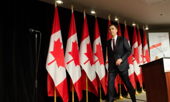 Finance Minister Bill Morneau leaves the stage after speak with reporters about his first budget March 22 in Ottawa. (Matthew Little/Epoch Times)