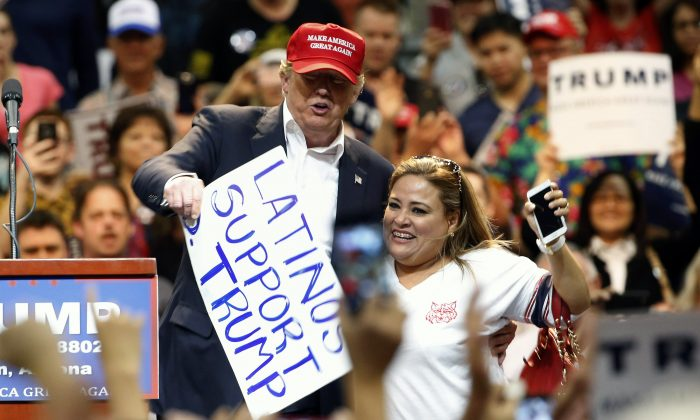 Republican presidential candidate Donald Trump, left, brings a supporter up on stage because he liked her sign as Trump speaks during a campaign rally Saturday, March 19, 2016, in Tucson, Ariz. (AP Photo/Ross D. Franklin)
