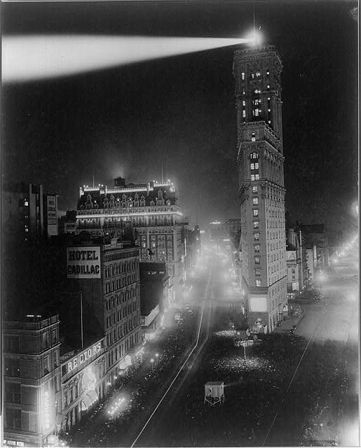 """The great white way"" B'way south from 42nd St. Photograph showing Broadway at night, with crowds gathered to see films projected outdoors.(Library of Congress)"