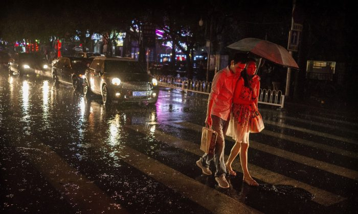 A Chinese couple walk together under an umbrella on a rainy evening on September 4, 2014 in Beijing, China.  (Photo by Kevin Frayer/Getty Images)
