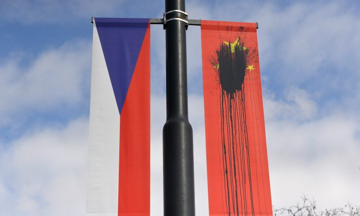 A Czech National flag hangs next to a Chinese National flag splattered with a black substance in Prague on March 26, 2016. (MICHAL CIZEK/AFP/Getty Images)