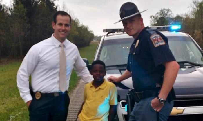Third-grade student Christopher Wheeler with a police officer (Alabama Law Enforcement Agency)