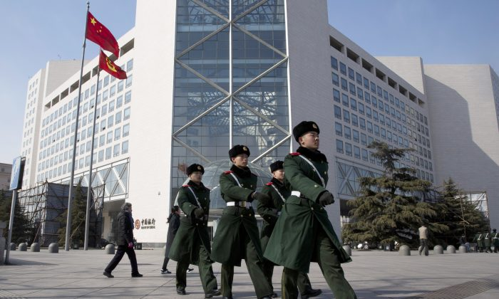Chinese paramilitary policemen march outside the Bank of China headquarters in Beijing, China, on Feb. 25, 2016.  (AP Photo/Ng Han Guan)