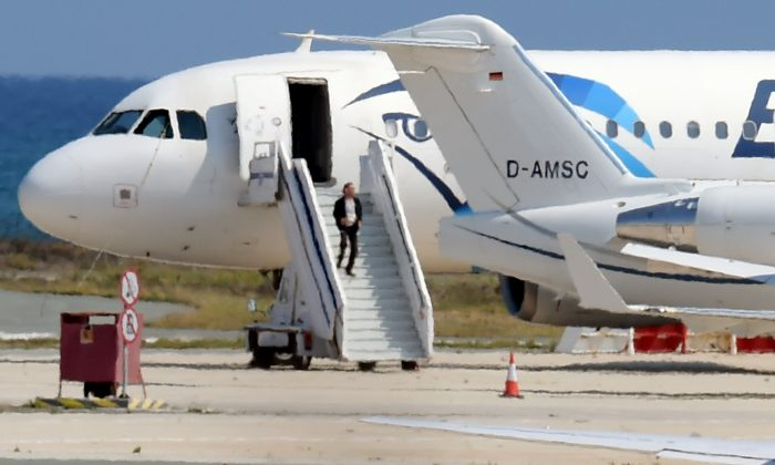 A man believed to be the hijacker of the EgyptAir Airbus A-320, which was diverted to Cyprus, leaves the plane before surrendering to security forces after a six-hour standoff on the tarmac at Larnaca airport's largely disused old terminal on March 29.  The hijacker has been detained. (GEORGE MICHAEL/AFP/Getty Images)