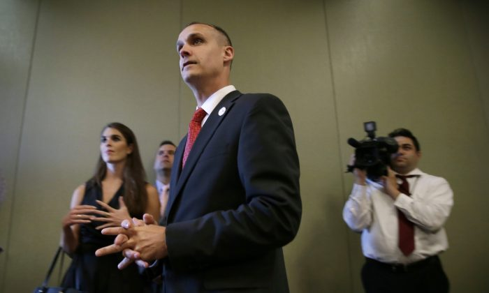 In this photo taken Aug. 25, 2015, Republican presidential candidate Donald Trump's campaign manager Corey Lewandowski watches as Trump speaks in Dubuque, Iowa. (AP Photo/Charlie Neibergall)