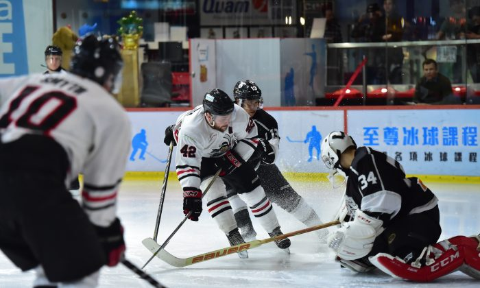 Eric McKenna (42) of Kowloon Warriors is thwarted by Soputh China Sharks goalie Emmerson Keung (34) and  Craig Rossel (13) while Greg Smyth (10) is in perfect position to receive a pass, during the first playoff match between Sharks and Warriors at Mega Ice on Thursday March 24, 2016. (Bill Cox/Epoch Times)