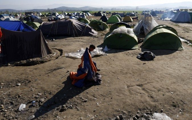 A boy plays with an abandoned tent in the makeshift refugee camp at the northern Greek border point of Idomeni, Greece, Thursday, March 31, 2016. (AP Photo/Darko Vojinovic)