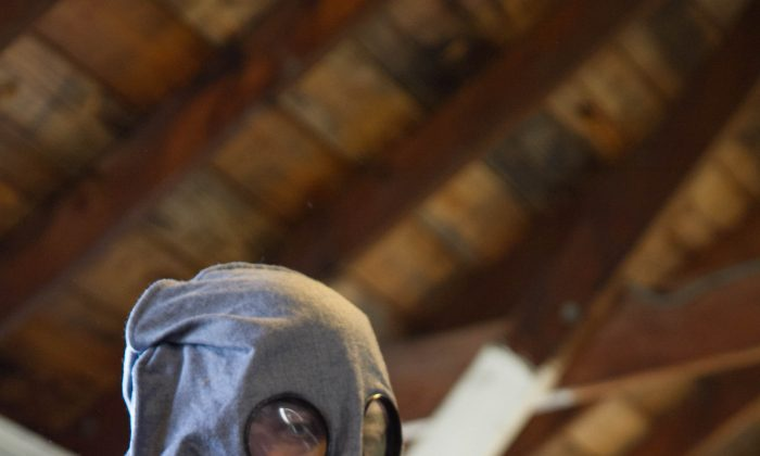 Tom Carton dressed as a soldier from the British 2nd Battalion of the Royal Sussex Regiment wears a gas mask from WWI during a presentation on chemical warfare at Museum Village in Monroe on April 2, 2016. The mask was soaked in an anti-gas agent to protect soldiers from gasses the Germans used, and while it may have saved the soldier from immediate death, they weren't necessarily fit to serve anymore. (Holly Kellum/Epoch Times)