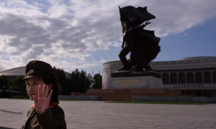 A uniformed tour guide gestures to tourists outside the War Museum in Pyongyang on October 9, 2015. North Korea is gearing up for a lavish celebration marking the 70th anniversary of its ruling Workers' Party on October 10.     AFP PHOTO / Ed Jones        (Photo credit should read ED JONES/AFP/Getty Images)