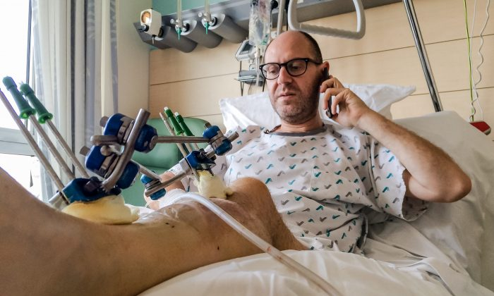 Walter Benjamin makes a phone call as he rests in his bed in Jette University Hospital in Brussels, April 3, 2016. Benjamin survived the Brussels airport attack but lost a leg. (AP Photo/Helene Franchineau)