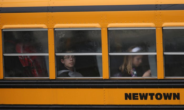 Children return to school on December 18, 2012 in Newtown, Connecticut. Four days after 20 children and six adults were killed at Sandy Hook Elementary School. (Photo by John Moore/Getty Images)