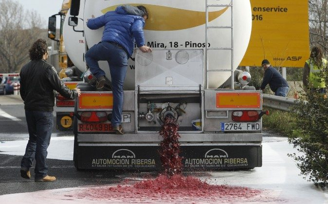 French winemakers open the tap of a Spanish truck's wine tanker on April 4, 2016 in Le Boulon, ten kilometers forms the French-Spanish border, during a demonstration against southern countries' wine imports. (RAYMOND ROIG/AFP/Getty)