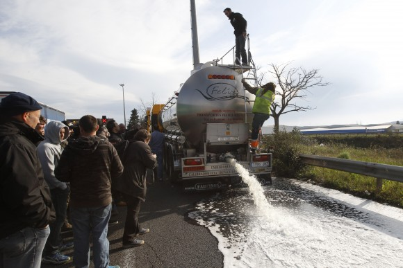 French winemakers watch wine flowing from the tap of a Spanish truck's tanker on April 4, 2016 in Le Boulon, ten kilometers from the French-Spanish border, during a demonstration against southern countries' wine imports. (RAYMOND ROIG/AFP/Getty)
