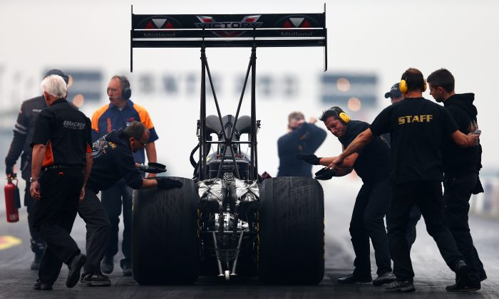 Team members scuff the car's tyres as they roll it back before launching a run during the Top Fuel Car qualifying for the European Drag Racing Championships at Santa Pod Raceway on September 5, 2014 in Podington, England. (Dan Istitene/Getty Images)
