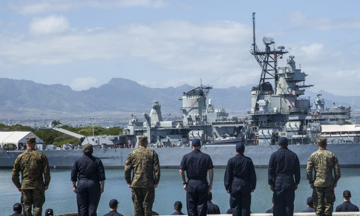 U.S. Marines and Sailors stand at attention in preparation to render honors to the Pearl Harbor memorial on Feb. 23. A Navy officer is being charged for spying on behalf of China. (U.S. Marine Corps/Lance Cpl. Alvin Pujols)