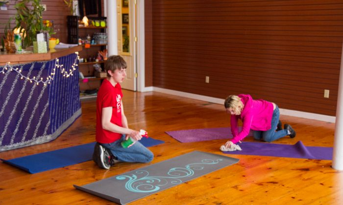 Christoper Ullrichs, a resident of Port Jervis (L), and Lori Rodriguez, a resident of Pine Bush, clean yoga mats during their internship at Happy Buddha Yoga studio in downtown Goshen on March 18, 2016. Both Ullrichs and Rodriguez are part of OU-BOCES' Including Communities program that started in November downtown Goshen. (Holly Kellum/Epoch Times)