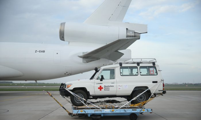 A 4X4 jeep of the German Red Cross (DRK), part of a 25-ton shipment of tents, generators, air-conditioning units, chlorine for disinfection and other supplies destined for Ebola treatment centers in Sierra Leone, stands on the tarmac shortly before ground crews loaded it onto a plane at Schoenefeld Airport on November 4, 2014 in Schoenefeld, Germany. (Sean Gallup/Getty Images)