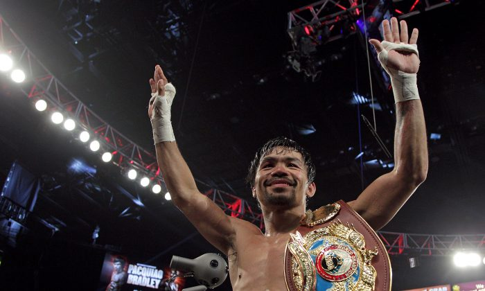 Manny Pacquiao gestures to fans celebrating after defeating Timothy Bradley Jr. in a 12-round unanimous decision at the MGM Grand Arena on April 9 in Las Vegas, Nevada. (John Gurzinski/AFP/Getty Images)