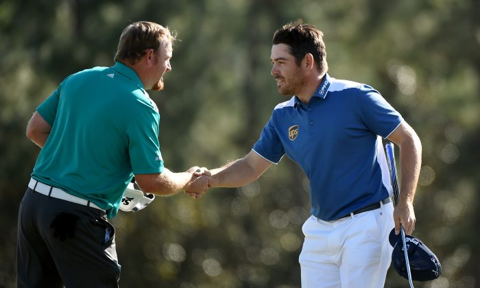J.B. Holmes (L) and Louis Oosthuizen shake hands after finishing on the 18th green during the final round of the 2016 Masters Tournament at Augusta National Golf Club. (Harry How/Getty Images)