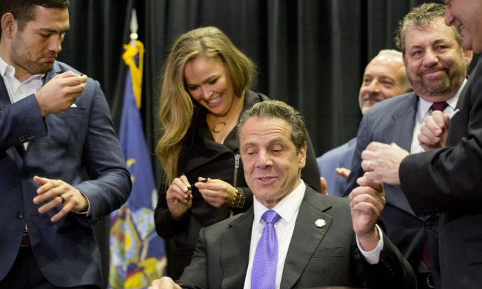 Gov. Andrew Cuomo, center, hands out souvenir pens after signing into law a measure that will allow professional mixed martial arts in New York, Thursday, April 14, 2016. Behind him are UFC athletes Chris Weidman, left, and Ronda Rousey, and James Dolan, executive chairman of Madison Square Garden. New York was the last U.S. state to prohibit the bouts. (AP Photo/Mark Lennihan)