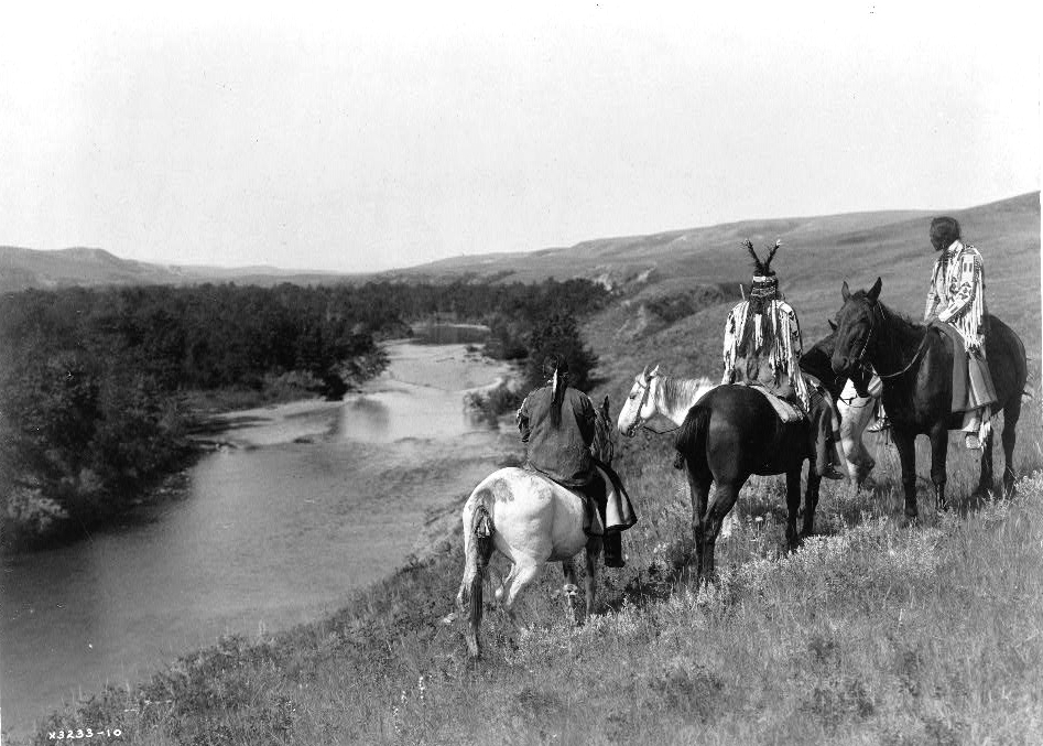 Three Piegan Indians and four horses on hill above river, 1910. (Edward S. Curtis/Library of Congress)