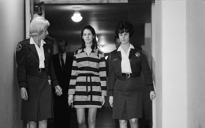 """Leslie Van Houten, 19, a member of Charles Manson's """"family"""" who is charged with the murders of Leno and Rosemary LaBianca, is escorted by two deputy sheriffs as she leaves the courtroom in Los Angeles, Dec. 19, 1969. (AP Photo/George Brich)"""