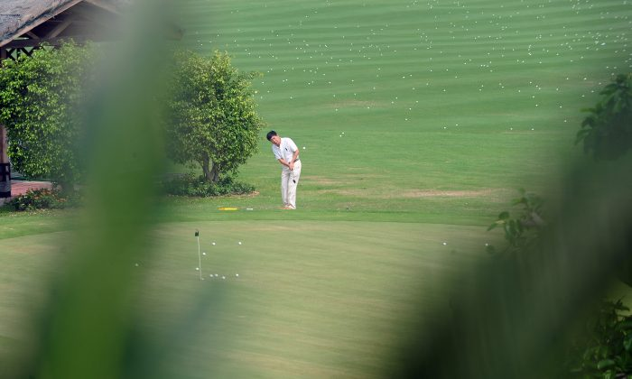 """A golfer practices his chip shot at a course in Sanya on Oct. 25, 2009. On April 12, 2016, the Chinese Communist Party's anti-corruption agency said that golf as a sport is """"neither right nor wrong."""" (FREDERIC J. BROWN/AFP/Getty Images)"""
