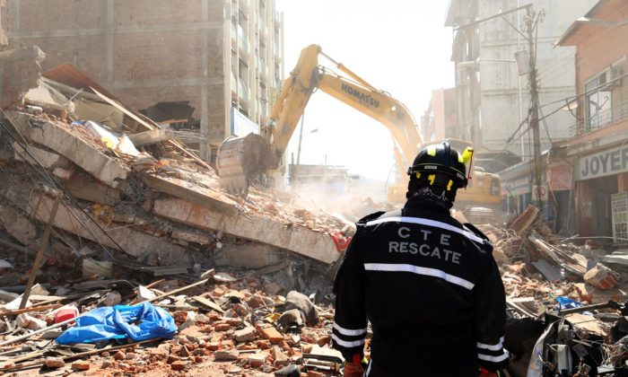 A rescue worker looks as heavy machinery removes the debris of a collapsed building in Portoviejo, Ecuador, on April 17, 2016. A magnitude-7.8 quake, the strongest since 1979, hit Ecuador flattening buildings, buckling highways along its Pacific coast and killing hundreds. (AP Photo/Carlos Sacoto)