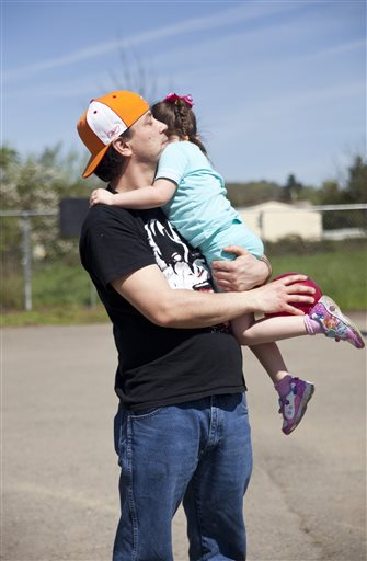 In this photo taken Saturday April 2, 2016, Bryan Thouvenel holds his daughter Harmony Thouvenel, 5, after playing ball in front of their home in Myrtle Creek, Ore. (Katie Alaimo/The News-Review via AP) MANDATORY CREDIT