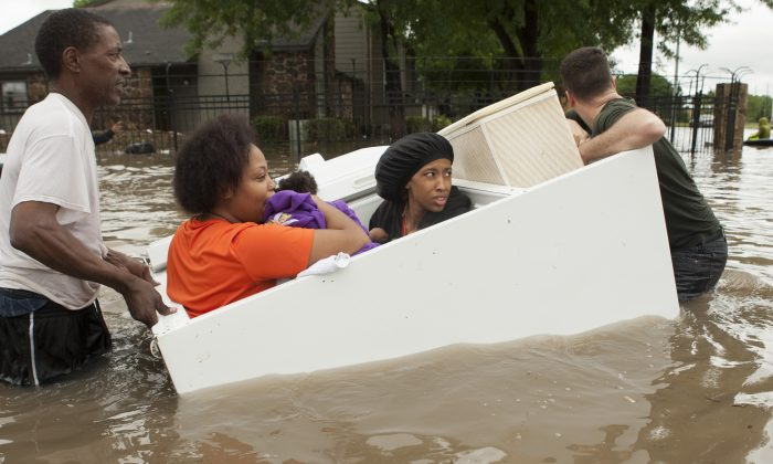 Residents of the Arbor Court apartments evacuate their flooded apartment complex in a refrigerator on Monday, April 18, 2016, in Houston. (Brett Coomer/Houston Chronicle via AP)