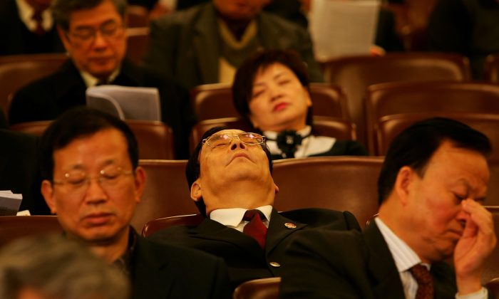 Chinese delegations sleep as they attend the opening session of the National People's Congress, or parliament, on March 5, 2007 in Beijing, China.  (Photo by Guang Niu/Getty Images)