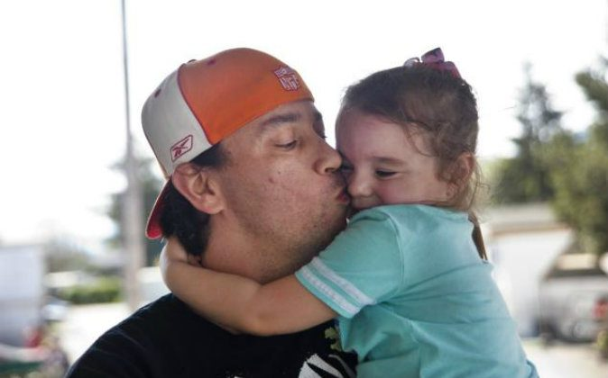 Bryan Thouvenel gives his daughter Harmony Thouvenel, a kiss while standing for a portrait in front of their home in Myrtle Creek, Ore on April 2, 2016,. They had been apart nearly two years when Thouvenel, thanks to a tip from a friend, found his daughter and estranged ex-girlfriend at a Salvation Army homeless shelter in Spokane, Wash. (Katie Alaimo/The News-Review via AP)