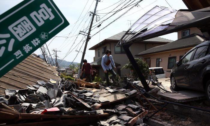 A man walks past the rubble of a collapsed house following an earthquake, on April 20, 2016 in Mashiki near Kumamoto, Japan. As of April 20, 48 people were confirmed dead after strong earthquakes rocked Kyushu Island of Japan. (Photo by Carl Court/Getty Images)