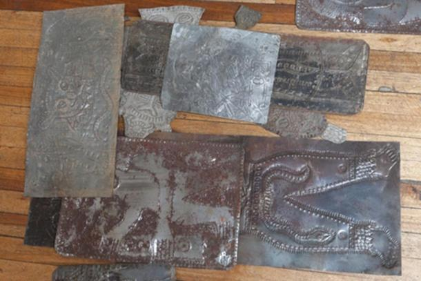 Carved metallic plates from Father Crespi's collection strewn on the floor in a dilapidated old building. (Ancient-Origins.net)