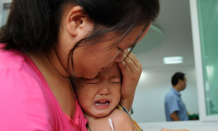 A Chinese girl cries in her mother's arms as she gets inoculated against measles as part of a free 10-day nationwide campaign to urge parents to participate amid public fears about the safety of the inoculations in Hefei, in eastern China's Anhui province on Sept. 11, 2010. (STR/AFP/Getty Images)
