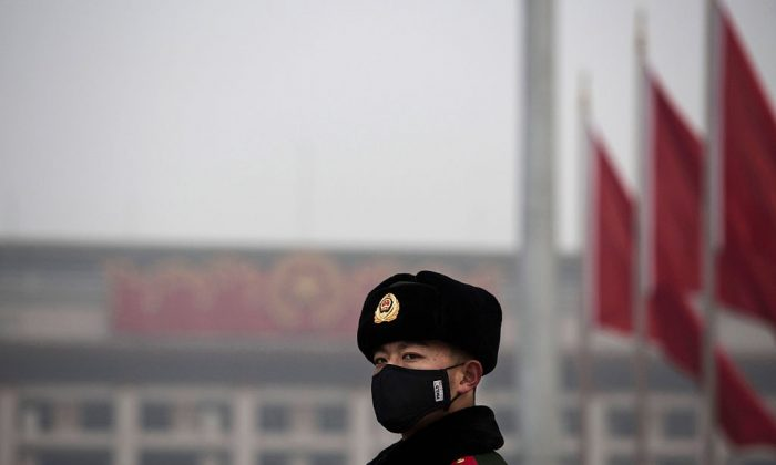 A Chinese paramilitary police officer wears a mask to protect against pollution in Tiananmen Square on Dec. 9, 2015 in Beijing, China. (Kevin Frayer/Getty Images)