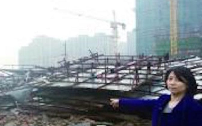 Ms. Shi standing next to her demolished house. (via Modern Express)